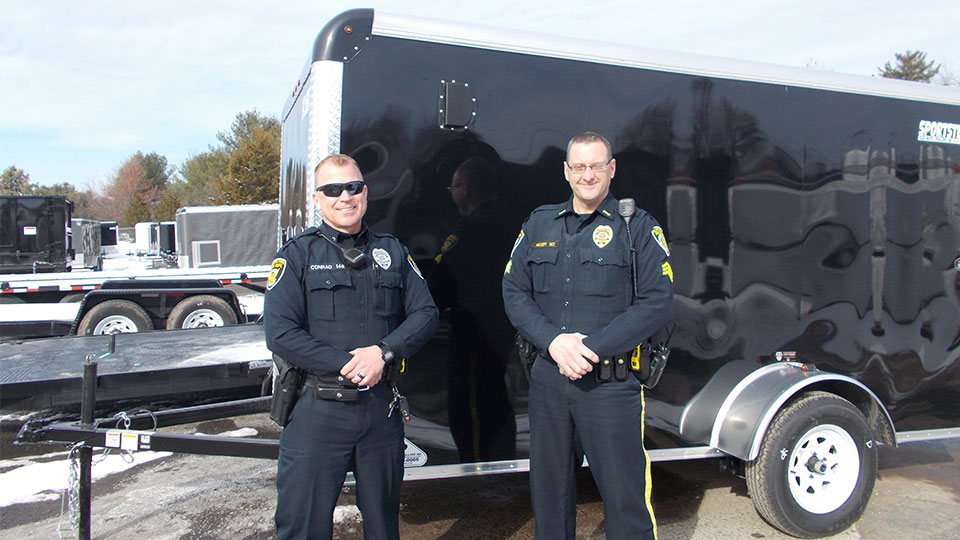 law enforcement standing next to an enclosed cargo trailer
