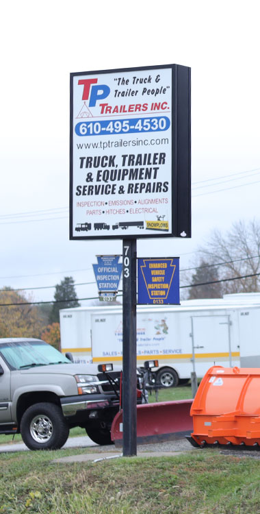 The front signage of TP Trailers with trailers and snow plow equipment at their location in Limerick, PA